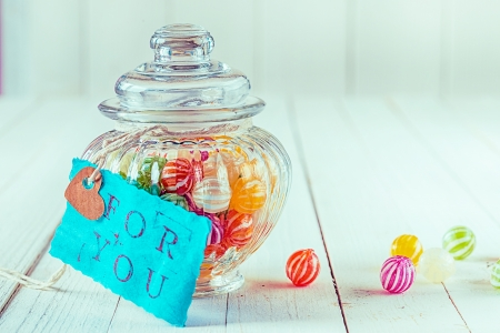 Close-up view of an antique candy jar filled with colorful candies with a blue tag with a romantic, For You, written on a wooden background photo