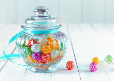 Colourful multicoloured striped candy in a decorative glass jar with a ribbed bulbous shape and a blue ribbon around the neck for a festive gift photo