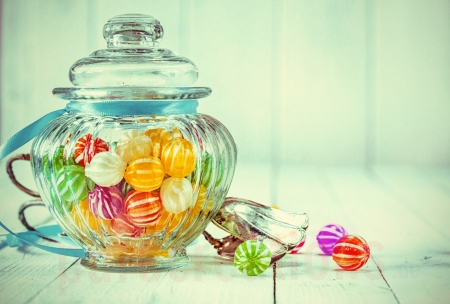 Low-angle view of an antique candy jar filled with colorful candies and ornate metal tongs on a wooden background photo