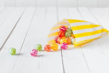 golosinas: Amarillo bolsa de caramelo rayado derramar sus dulces sobre una mesa de madera blanca Foto de archivo