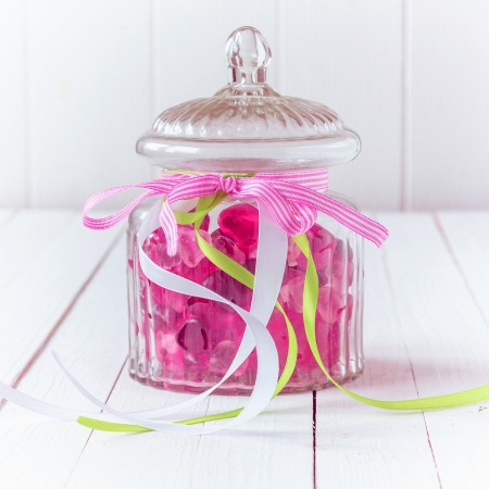 Antique glass candy jar filled with pink gummy candies and tied with three ribbons with the white, green and pink colors over a white wooden board background photo