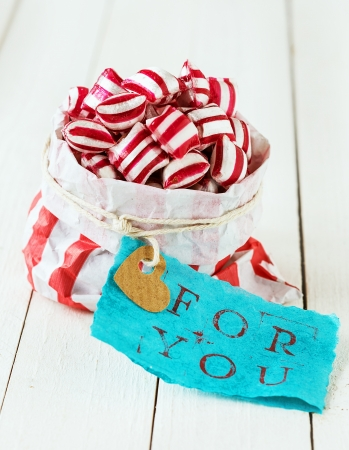Colourful red and white striped candy heaped to overflowing in a matching striped paper packet with a blue gift label with the words For You on a background of white wooden boards Stock Photo