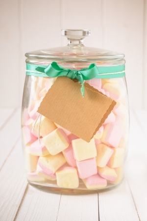 Old glass candy jar filled with square pink and yellow marshmallows and a blank tag tied with a green ribbon over a white wooden background Imagens