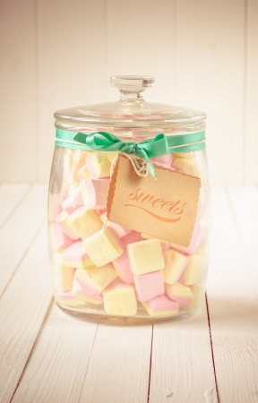 Old glass candy jar filled with square pink and yellow marshmallows and a tag tied with a green ribbon over a white wooden background Stock Photo - 20280977