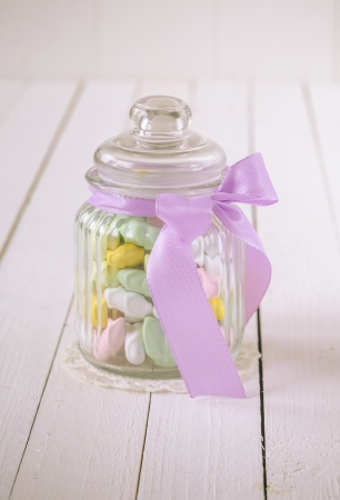 Antique glass candy jar filled with colorful sugar covered almonds and a violet bow over a white wooden background