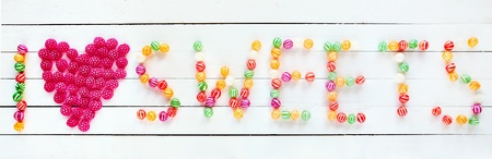 I love sweets written with several types of candies over a white wooden board background photo