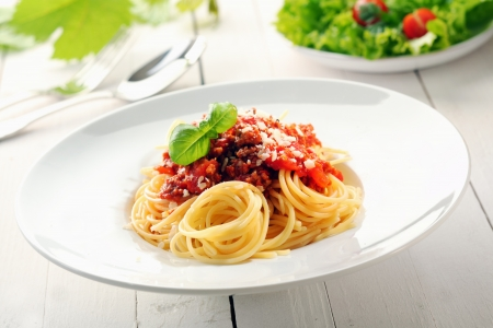 Plate of spaghetti bolognaise with a delicious sauce of tomatoes and minced beef garnished with basil