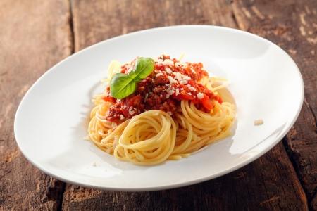 Italiaanse spaghetti overgoten met bolognaise of bolognese, saus met tomaten, vlees en kaas op een effen witte plaat