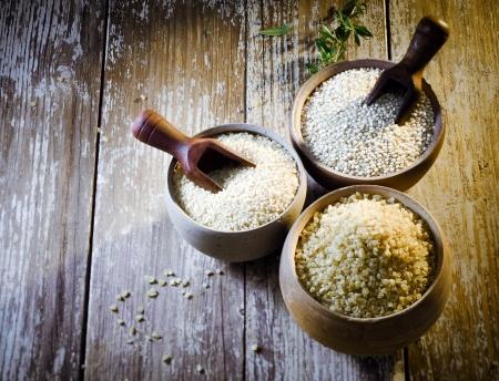 乾燥のブルガーと砕いたデュラム ・ セモリナ小麦・ キノアで作ったクスクスを含む 3 つの土器素朴なポットのハイアングルの種子、アカザ科高蛋 写真素材