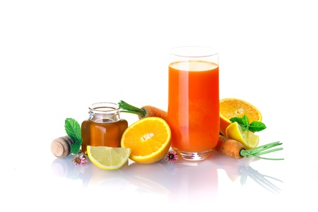 some: Glass of healthy carrot and citrus cocktail sweetened with honey and surrounded by fresh juicy oranges and limes, a jar of honey and whole carrots on white Stock Photo