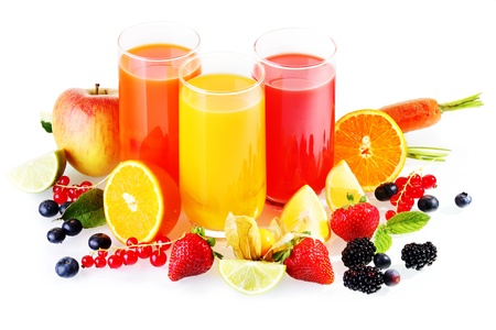 fruit drinks: Colourful glasses of healthy fresh drinks from liquidised fruit and vegetables with an array of colourful fresh fruit around the glasses on a white background