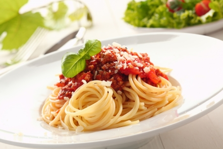 bolognaise: Close up low angle view of a plate of twirled spaghetti topped with delicious bolognaise sauce and basil Stock Photo