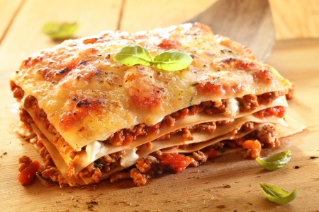 Golden lasagne with meat, tomatoes, cheese sauce and pasta in alternating layers on a wooden board garnished with basil Stock Photo