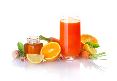 Fresh fruit and vegetable juice made from a blend of healthy honey, citrus fruits and carrots in a colourful still life on white