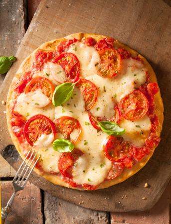 liggande: Overhead bild av en helt oklippt härlig färsk ost och tomat pizza på en planka