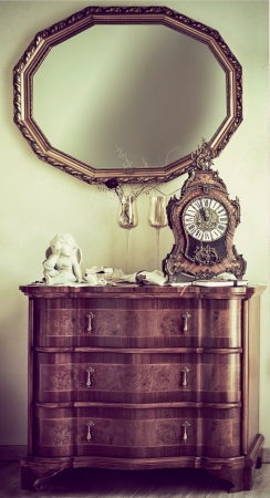 wall mirror: Antique wooden commode with a baroque style ornate mantel clock and wooden framed wall mirror for a vintage style interior design