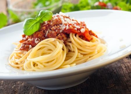 Lage hoek weergave van een portie van Italiaanse spaghetti met een op basis van vlees bolognese, of bolognaise, saus op een effen witte plaat Stockfoto