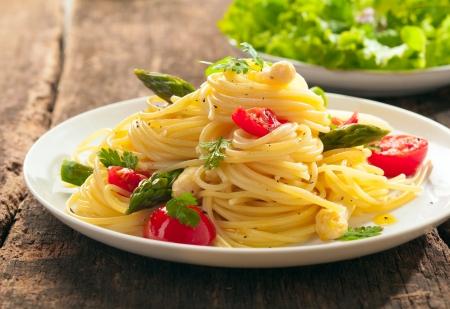 新鮮なグリーン アスパラガス、トマトがイタリアのスパゲティのプレートの低角度のビューは、緑豊かなグリーン サラダを添えてください。