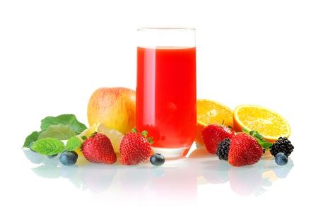 Glass of healthy blended fresh fruit juice cocktail surrounded by fresh apple, oranges and berries including strawberry, blackcurrant and blueberry Stock Photo