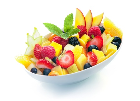 fruity salad: Bowl of colourful exotic tropical fruit salad with a sprig of fresh mint on a white background
