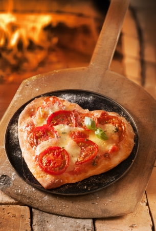 pizza oven: Romantic heart shaped Italian pizza on a platter and wooden board with the fire of a pizza oven visible behind