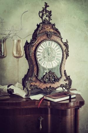 reloj de pendulo: Antiguo reloj de manto adornado con un caso con incrustaciones de estilo barroco y de línea de lujo en la parte superior de un inodoro con un diario o revista en un concepto de gestión del tiempo
