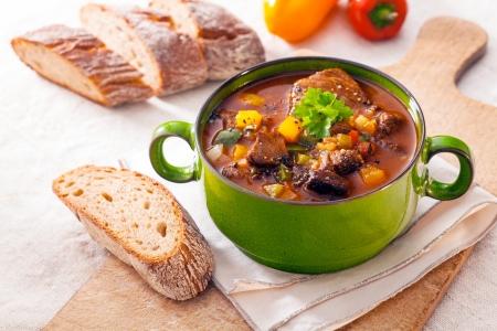 풍부한 육즙의 고기와 모듬 야채와 녹색 금속 냄비에 맛있는 겨울 스튜 나무도 마 보드에 신선한 피 각 질의 빵 역임