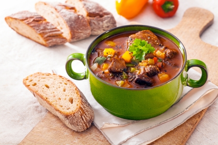 Tasty winter stew in a green metal pot with meat and assorted vegetables in a rich gravy served with fresh crusty bread on a wooden chopping board