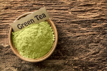 flavouring: Overhead view of a small bowl of ground green tea powder with a name label used as a beverage and a flavouring in cooking on textured wood with copyspace Stock Photo