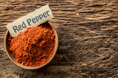Bowl of spicy hot red cayenne pepper, a pungent aromatic spice and cooking ingredient, with a decorative name tag on an old weathered wood surface, overhead view Stock Photo - 21988629