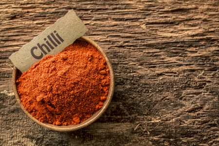 Red hot chilli powder in a rustic wooden bowl with an ornamental name label on a grunge weathered textured wooden surface, overhead view Stock Photo - 21988638