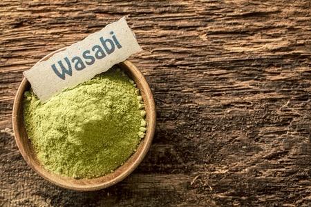 pungent: Wasabi, un pungente condimento verde giapponese fatta dalla radice della pianta Eutrema wasabi, essiccato e in polvere in una ciotola in piedi su un vecchio weathered superficie con copyspace