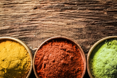 Close up overhead view of bowls of freshly ground curry, chilli and milled green tea, or matcha, spices on a textured wood background with copyspace Stock Photo - 21988699