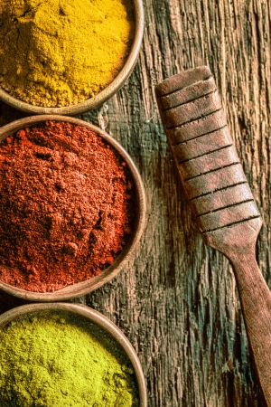 chilli: Closeup partial overhead view of bowls of ground green tea or matcha, chilli and curry spices with an old vintage wooden kitchen spatula on a textured wood background