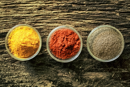 Overhead view of three open spice containers with colourful curry, chilli powder or red pepper on an old aged weathered wooden background with copyspace Stock Photo - 21988717