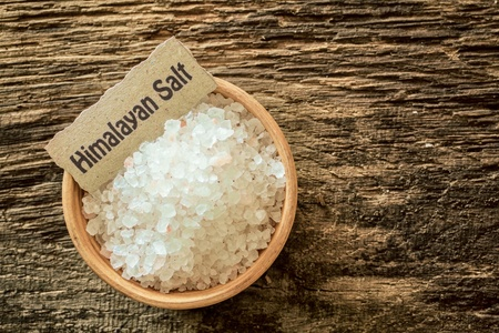 Himalayan salt crystals, a rock salt from the mines in Pakistan, in a bowl with a name label on a grunge textured wood surface, overhead view Stock Photo - 21988736
