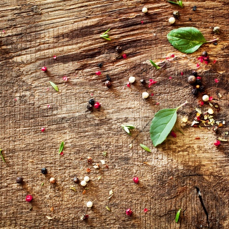 remnants: Scattered peppercorns and fresh green basil leaves lying on a textured wooden kitchen counter, the remnants of spices and herbs from preparing a meal Stock Photo