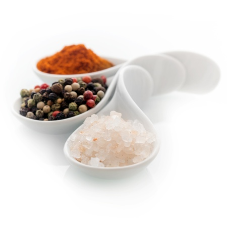Ceramic spoons filled with natural Himalayan rock salt, whole dried black peppercorns and hot red cayenne pepper on a white background
