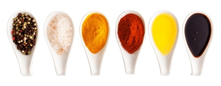 Salt, spices and olive oil border or banner with the colourful ingredients in white ceramic spoons arranged in a horizontal row Stock Photo