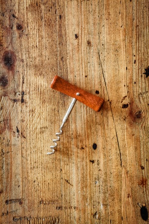 Manual corkscrew with a wooden handle and steel screw for opening bottles of wine lying centred on a textured wooden surface with copyspace photo