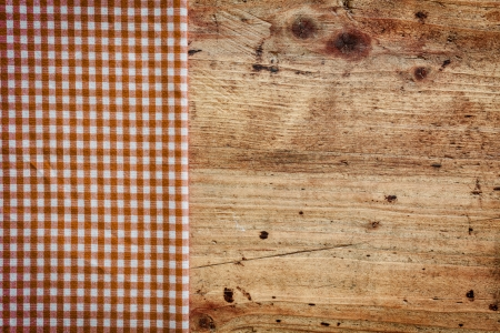 country kitchen: Wood background with copyspace bordered with a red and white checked napkin conceptual of an old country kitchen
