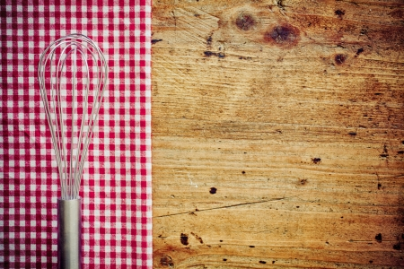 menu tool: Metal cooking whisk, or balloon whisk, lying on a fresh red and white checkered napkin on a wooden countertop in a rustic kitchen with copyspace Stock Photo