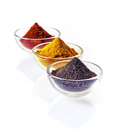Three clear glass bowls of colourful of ground spice and black lava salt in conical heaps arranged in a receding row on a white background photo