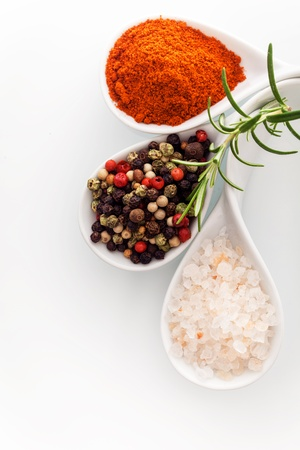 Overhead view of Himalayan rock salt, red cayenne pepper and black peppercorns in ceramic spoons with a sprig of fresh rosemary photo