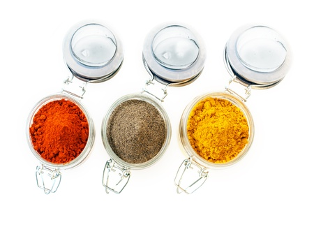 Jars of colourful ground spice viewed from above with red cayenne pepper or chilli powder, curry and black pepper, isolated on white photo