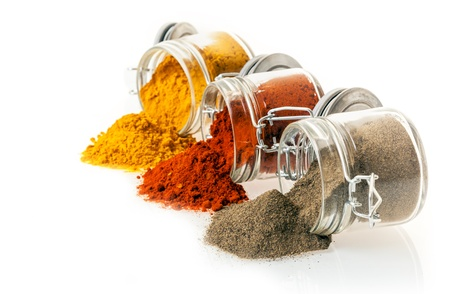 curry powder: Colourful ground spices spilling from glass jars onto a white background with chilli pepper, curry powder and ground black pepper with copyspace
