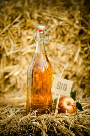 A bottle of natural apple cider vinegar next to a fresh apple on straw, tagged as