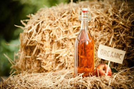 tagged: A bottle of natural apple cider vinegar on straw, tagged as organic Stock Photo