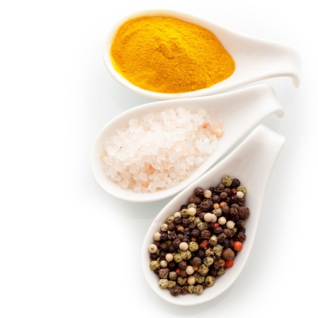 Coarse fresh Himalayan rock salt, dried black peppercorns and curry powder, a group of culinary spices in white ceramic spoons over a white background Reklamní fotografie