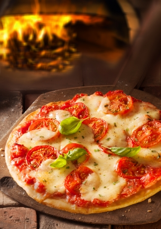 Delicious Italian pizza topped with melted cheese and tomato in a pizzeria with the fire from the oven visible behind photo